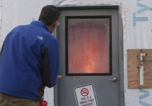 Man looking at a fire test behind a closed door.